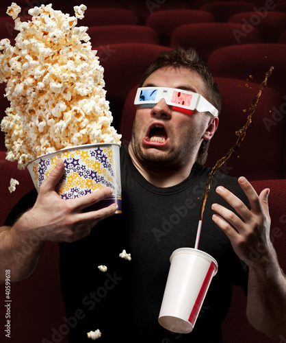 Very scared man watching 3D movie