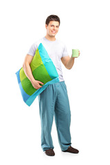 Smiling male holding a pillow and cup of coffee