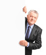Smiling mature businessman holding a white panel and gesturing