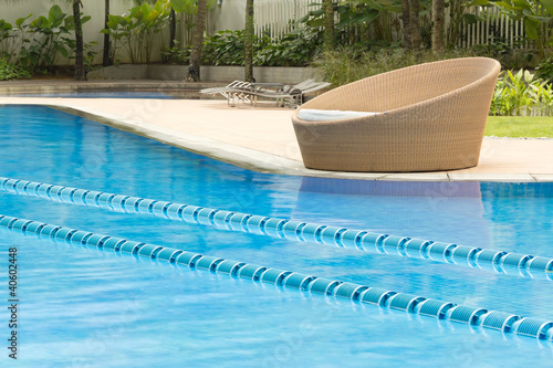Crystal cline swimming pool with round cozy chair on the side