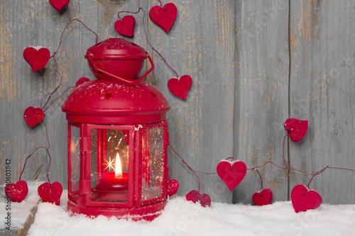 Rote Laterne mit Herzen im Schnee