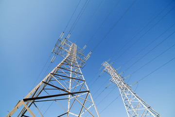 two electrical pylons on blue sky