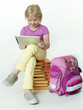 Pupil seated on books plays concentrated with tabletpc