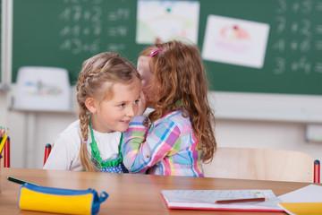 zwei mädchen flüstern in der schule
