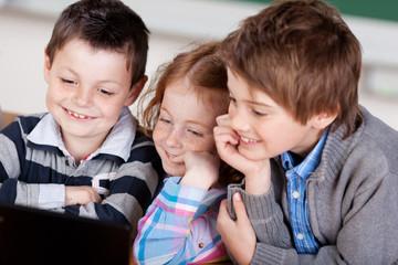 drei kinder schauen auf den laptop
