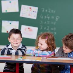 drei lachende kinder in der grundschule