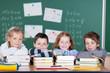 vier grundschüler stützen sich auf bücher