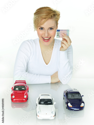 Woman shows her driver licence and her dream cars