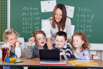lehrerin zeigt schülern etwas am laptop