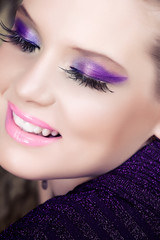 woman smiling with purple eyeshadow