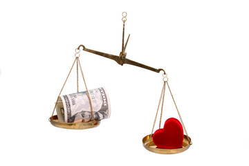 Money and heart on scales.