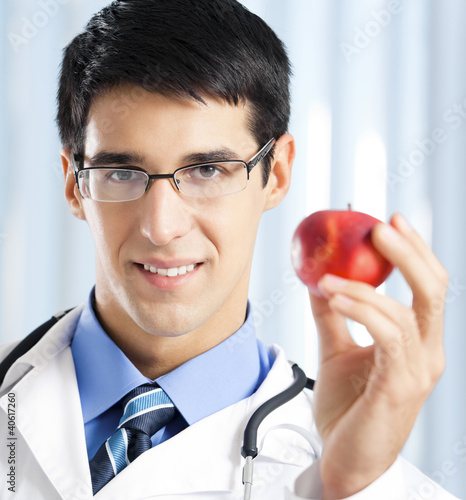 Smiling doctor with apple, at office