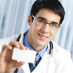 Doctor showing business card, at office