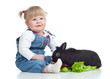 Funny little girl feeding a rabbit with lettuce on the floor
