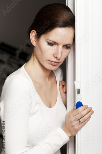 Sad woman with negative pregnancy test
