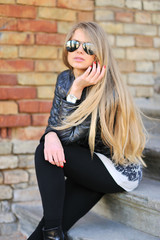 Portrait of young girl sitting on the stairs in sunglasses
