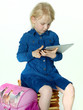 Cute little pupil plays concentrated with tabletpc