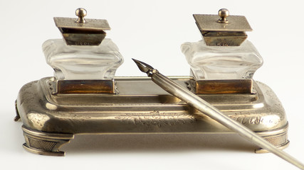 Old double glass and silver inkwell wiith pen isolated on white