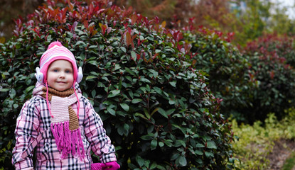 Pretty girl in a pink plaid polto a walk in the park