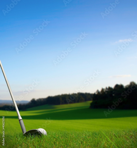 hitting golf ball with club towards green