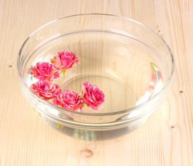 Bowl with roses on wooden background