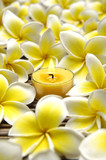 Yellow candles and frangipani flower on mat