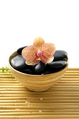 Wooden bowl of stones and orchid on mat