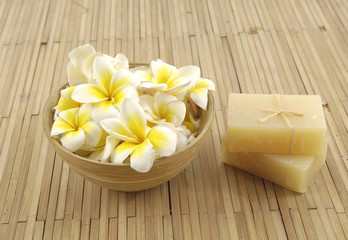 frangipani flower in bowl with natural handmade soap onmat