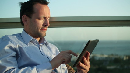Businessman sitting outdoors and using tablet computer