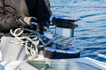 Crew work with genoa sheet rope and winch on sailing boat.
