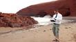 Angry businessman chatting on tablet on beautiful Legzira beach