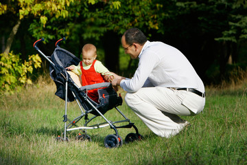 father and baby in stroller on natural background