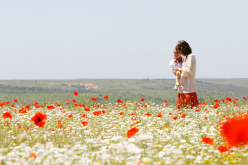 mother and son in traditional clothes in flower field