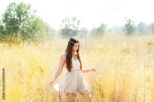 Asian indian woman walking in golden dried field