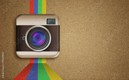 retro camera icon with rainbow colors on corkboard background