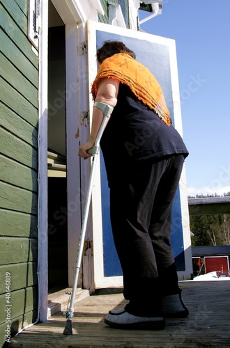 Disabled woman with crutch entering her house