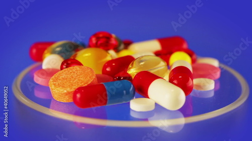 Pills and tablets heap rotating on blue, loop ready