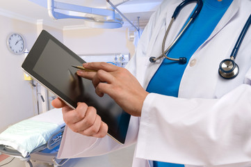 Doctor pointing on tablet PC at emergency room