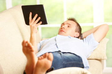 Relaxed man using tablet