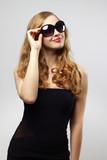 Fashionable lady wearing sunglasses on gray background