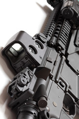 Modern tactical laser sght on assault carbine close-up.