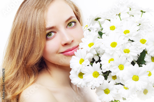 beautiful girl with white chrysanthemum on a light background