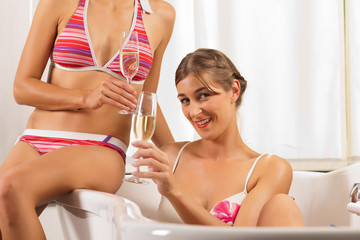 Wellness - female friends with champagne in bathtub