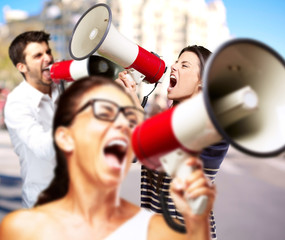 young friends screaming with megaphone against a building