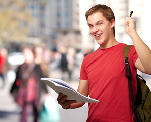 portrait of handsome student holding notebook and pen at crowded
