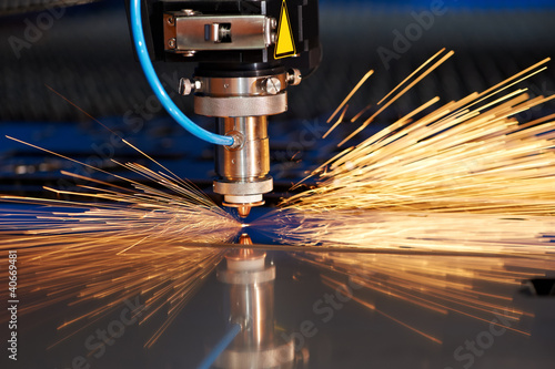 Leinwanddruck Bild Laser cutting of metal sheet with sparks
