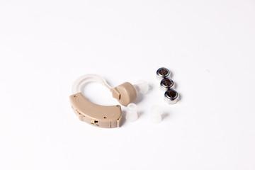 Ein Hörgerät mit Ersatzstöpseln und Batterien