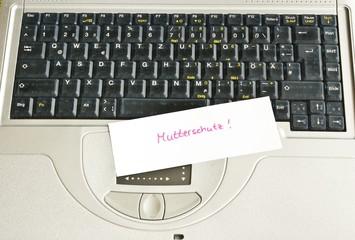 """Zettel """"Mutterschutz"""" auf Tastatur eines Laptops"""