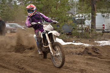 Biker leaves the track with a large plume of sand