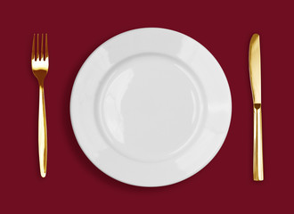 Golden knife, fork and white plate on red background